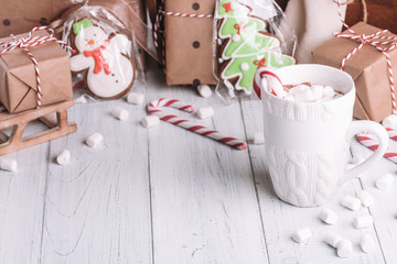 Cup of cocoa or chocolate on wooden Christmas background. Winter hot chocolate drink with marshmallows, snowman and a fir-tree cookies, candy canes