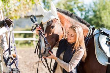 Girl equestrian rider equips horse. Horse theme