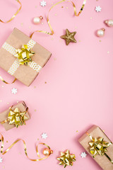 Christmas vertical composition with gold decor and kraft gifts on pastel pink background with copy space.