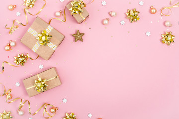 Christmas background with golden gift or present box and holiday decorations on pink pastel table. View from the top. Greeting card. Flat lay style.