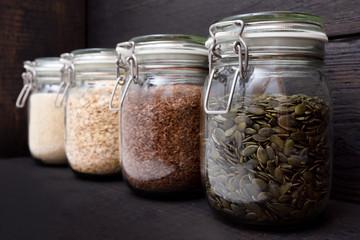 Various seeds in storage jars in pantry, dark wooden background. Smart kitchen organization Wall mural