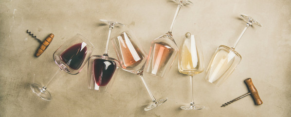 Flat-lay of red, rose and white wine in glasses and corkscrews over grey concrete background, top view, wide composition. Wine bar, winery, wine degustation concept Wall mural