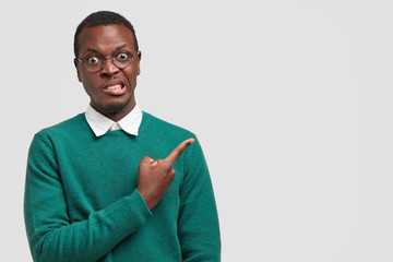 Puzzled dark skinned man clenches teeth, looks in disbelief, points at upper right corner, wears transparent glasses and sweater, models over white background with copy space for your advertisement