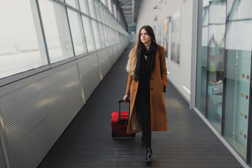 Businesswoman on airport talking on the smartphone while walking with hand luggage in train station or airpot going to boarding gate. Girl using mobile phone for conversation.