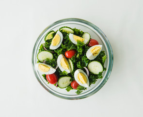 healthy kale salad with eggs, tomato, cucumber and avocado