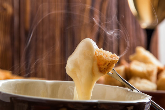 Close up, macro. Traditional french cheese fondue. Crouton dipped into stemy-hot cheese fondue on a long-stemmed fork. Copy space.