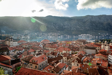 View of the roofs of the houses and the marina with a fortress wall in the old town of Kotor, Montenegro at sunset
