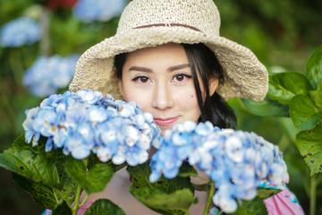 Beautiful girl with a field of hydrangea flowers.