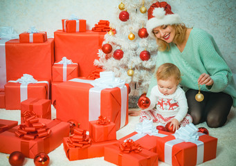 Funny kid baby with mom and Christmas gift. Christmas kids. Child with a Christmas present gift. Cute little kids celebrating Christmas.