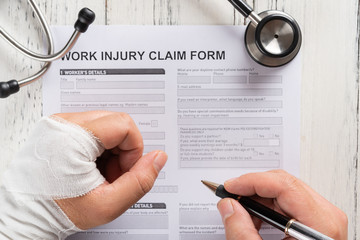 top view man filling up a work injury claim form with stethoscope  medical and insurance concept