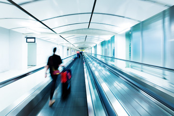 blurred people walking on a moving walkway, keep moving forward and travel concept