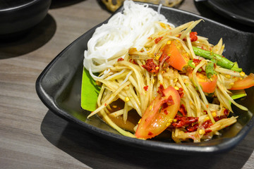famous and popular Thai street food, green papaya spicy salad with pickled fish or Som Tum served with Thai rice noodles in black plate on wooden table background