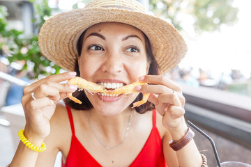 Happy Asian woman in hat eating local Spanish cuisine grilled seafood and prawns
