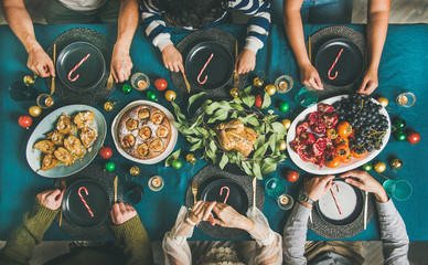 Company of friends of different ages gathering for Christmas or New Year party dinner at festive table. Flat-lay of people sitting with plates and ready to start celebrating holiday together, top view