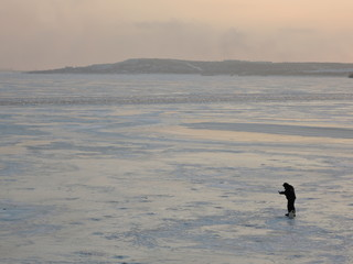 A winter fisherman on ice is fishing.
