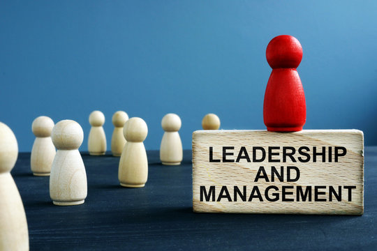 Leadership and management written on a wooden block.