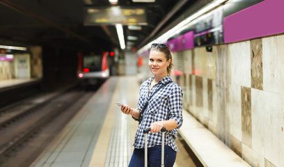 Portrait of girl with suitcase waiting for train