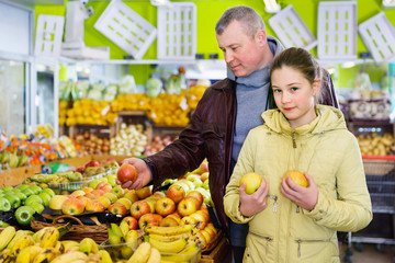 Girl with her father buying apples in fruit store