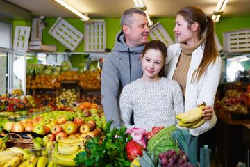 Nice family with daughter buying ripe bananas