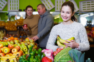 Positive girl with parents choosing fruits