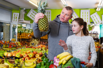 father and daughter buying together pineapple