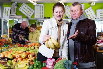Couple choosing bananas in market