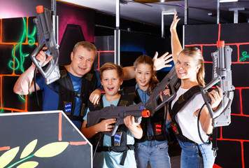 Group of happy teenagers and adults with laser guns posing together while having fun on lasertag arena