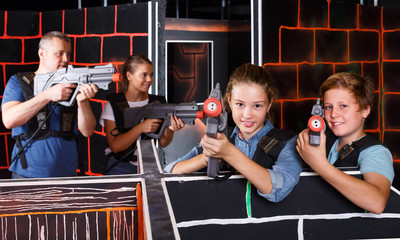 positive teen brother and sister with laser pistols playing laser tag with their parents