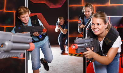 enthusiastic young parents and children with laser pistols playing laser tag