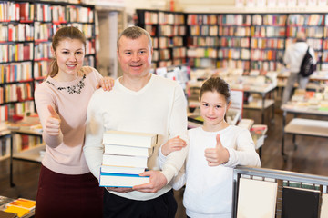 Happy family with daughter holding pile of books
