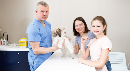 Happy family with dog consulting by veterinarian