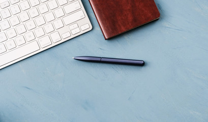 A keyboard, a blue pen and a notebook on a blue desk top.