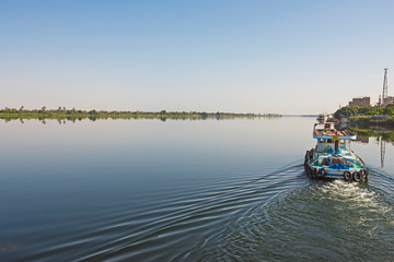 Tug boat towing yacht on nile river in Egypt