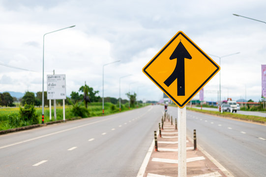 traffic sign, lanes merging left with soft-focus and over light in the background