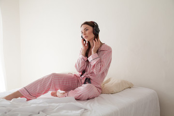 woman in pajamas on the bed listening to music headphones