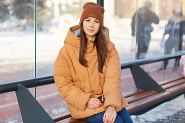 Outdoor shot of pleasant looking brunette, dressed in brown hat and jacket, sits at bus station, holds mobile phone, looks directly at camera, enjoys good day during winter. Street style concept