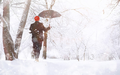 A man on a walk in the park. Young man with in the winter snowfall.