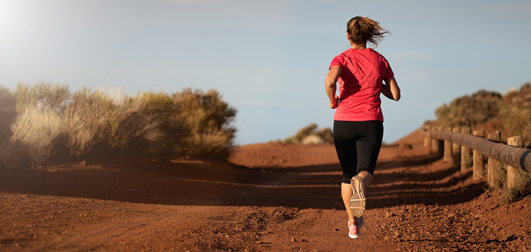 Fitness woman runner athlete running at road, working out cardio on nature landscape