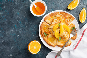 Crepes suzette - pancakes with orange sauce on dark blue background.