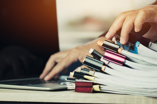 Businessman hands working in Stacks of paper files searching information business report papers and piles of unfinished documents achieves on laptop computer desk in modern office
