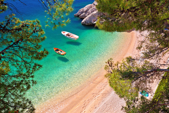 Hiden beach in Brela with boats on emerald sea aerial view
