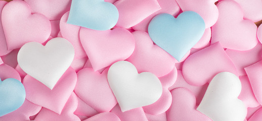 Valentine's Day. Pink heart shape backdrop. Abstract holiday Valentine background with pink, white and blue pastel color satin hearts. Love concept. Flat lay, top view