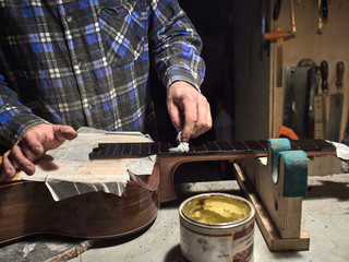 Installation frets on the neck of the guitar. The specialist impregnates with oil fingerboard.