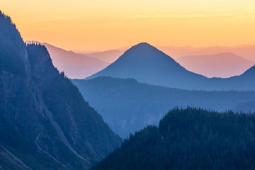blue mountain tops in front of hazy orange sunset