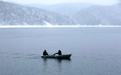 Men row boat across the Yenisei river during snowfall outside Krasnoyarsk