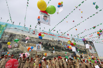 Palestinian Hamas boy scouts release balloons attached to pictures during a rally marking the 31st anniversary of Hamas' founding, in Gaza City