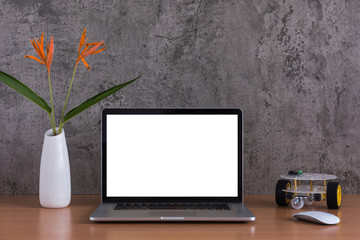 Blank screen of laptop computer, mouse, robot car and flowers vase on raw concreate background