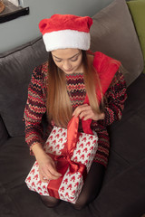 young woman sitting on the sofa, opens a present, top view