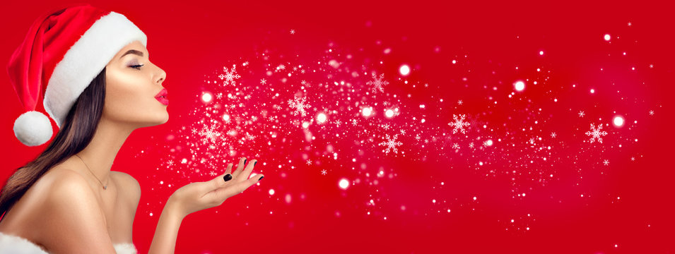 Christmas winter fashion girl on red background. Beautiful New Year and Xmas holiday makeup. Beauty model woman in Santa's hat blowing snow in her hand
