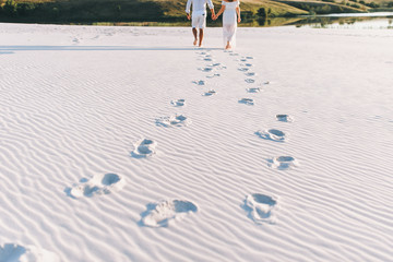 Footprints on the white sand from people in love. Love story. Foot prints. Newlyweds go hand in the desert. Conceptual photography.